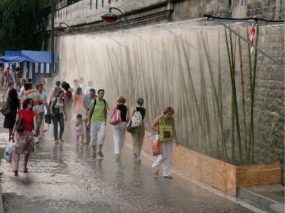 Gent passant per un jet d'aigua per la forta calor